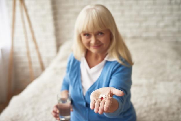 Gelukkige vrouw toont pillen in de menopauze.