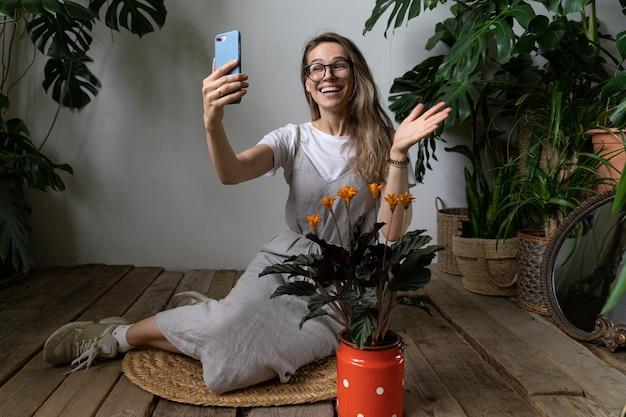 Gelukkige vrouw tuinman dragen linnen jurk, glimlachend en sprekend op videogesprek op smartphone, zeg hallo, zittend op een houten vloer in de buurt van bloeiende calathea plant in oude rode melk kan. huis & tuin