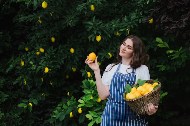 Gelukkige vrouw tuinman plukt citroenen in de tuin en sloot haar ogen met plezier
