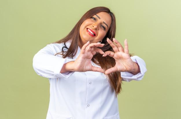 Gelukkige vrouw van middelbare leeftijd arts in witte jas met stethoscoop kijkend naar voorkant hart gebaar maken met vingers vrolijk lachend staande over groene muur