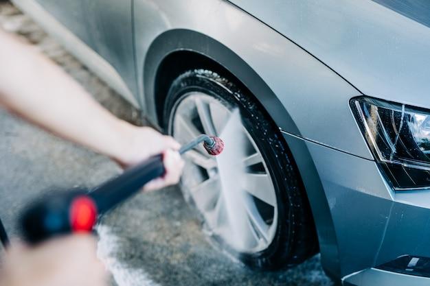 Gelukkige vrouw van middelbare leeftijd die auto wast bij autowasstation met behulp van hogedrukwatermachine.