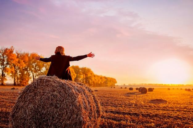 Gelukkige vrouw van middelbare leeftijd die op een hooiberg in het herfstveld zit en zich vrij voelt met geopende armen. ontspannen en genieten van de natuur bij zonsondergang