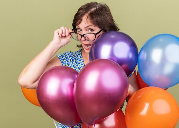 Gelukkige vrouw van middelbare leeftijd in een bril met een stel kleurrijke ballonnen verrast?