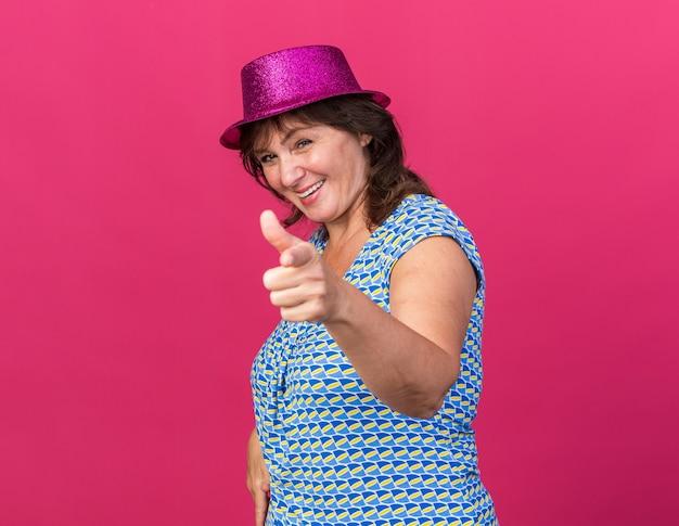 Gelukkige vrouw van middelbare leeftijd in feesthoed wijzend met wijsvinger glimlachend vrolijk verjaardagsfeestje vierend staande over roze muur