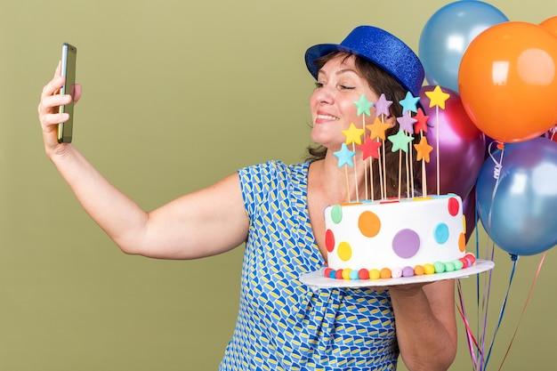 Gelukkige vrouw van middelbare leeftijd in feestmuts met een bos van kleurrijke ballonnen met verjaardagstaart die selfie maakt met smartphone om verjaardagsfeestje te vieren dat over groene muur staat