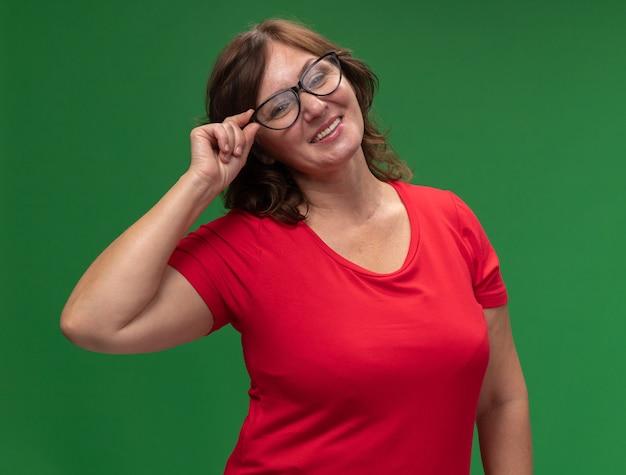 Gelukkige vrouw van middelbare leeftijd in rode t-shirt die glazen draagt die in grote lijnen over groene muur glimlachen