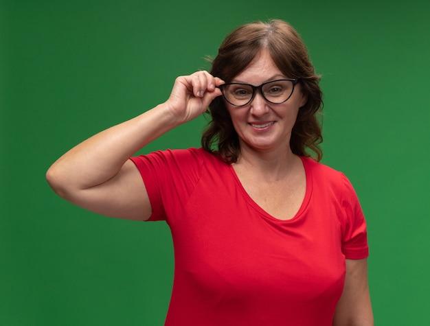 Gelukkige vrouw van middelbare leeftijd in rode t-shirt die glazen draagt die vrolijk permanent over groene muur glimlachen