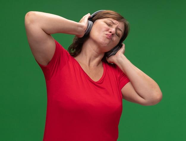 Gelukkige vrouw van middelbare leeftijd in rode t-shirt met koptelefoon die van haar favoriete muziek geniet die zich over groene muur bevindt