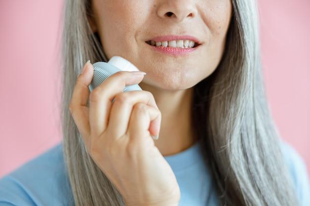 Gelukkige vrouw van middelbare leeftijd reinigt gezicht met sonische borstel staande op roze achtergrond
