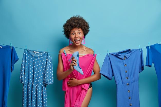Gelukkige vrouw verbergt achterste roze jurk hangend aan touw, verbergt het naakte lichaam, houdt blauwe schoenen met hoge hakken vast, kiest kledingstukken om zich aan te kleden, heeft een vrolijke uitdrukking. duizendjarig meisje bereidt zich voor op date