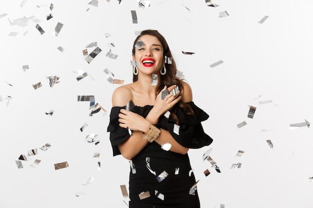 Gelukkige vrouw vieren nieuwjaar dansen in confetti, zwarte elegante jurk dragen, zorgeloos lachen, staande op witte achtergrond.