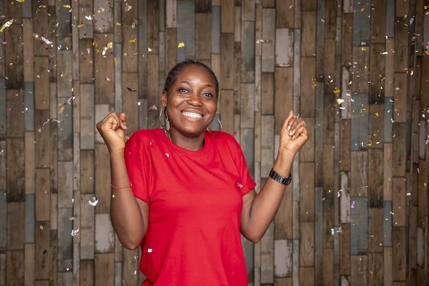 Gelukkige vrouw viert feest met confetti voor een houten muur