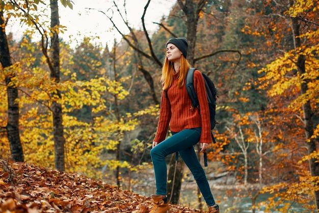 Gelukkige vrouw wandelaar met een rugzak op haar rug in spijkerbroek en een rode trui in het herfst bospark