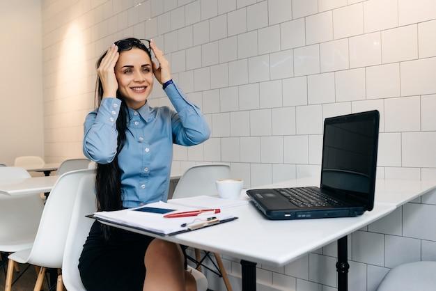 Gelukkige vrouw zit aan de balie in kantoor