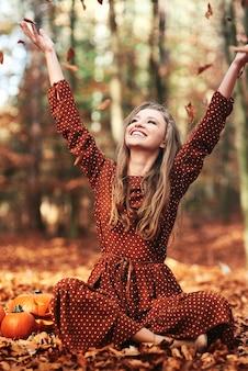 Gelukkige vrouw zit en gooit herfstbladeren in het bos