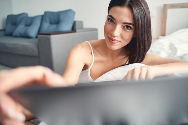 Gelukkige vrouw zit in de buurt van een bed met een glanzende glimlach en trekt het laptopscherm omhoog terwijl ze zich voorbereidt om aan het werk te gaan