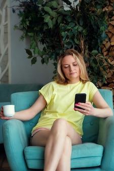 Gelukkige vrouw zit in een stoel in de woonkamer en surft op internet met een mobiele telefoon