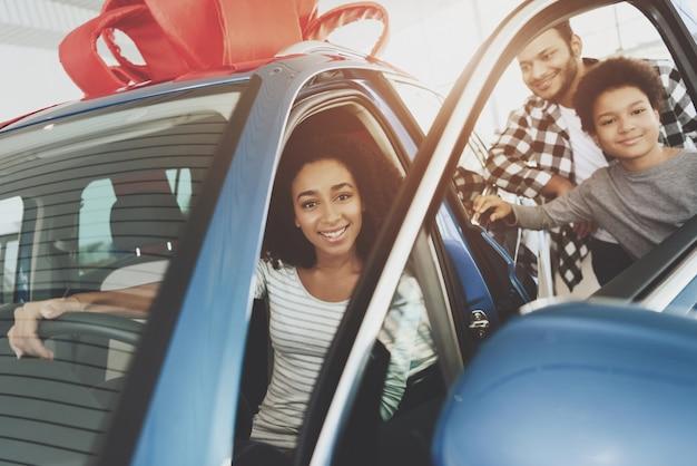 Gelukkige vrouw zit in geschenk auto deur is geopend.