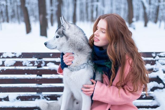 Gelukkige vrouw zittend op de bank met husky