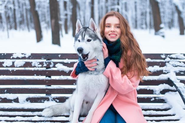 Gelukkige vrouw zittend op de bank met siberische husky