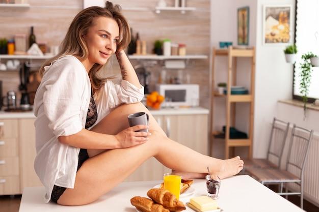 Gelukkige vrouw zittend op de keukentafel dragen van sexy lingerie kopje warme koffie te houden. provocerende jonge vrouw met tatoeages die verleidelijk ondergoed dragen.