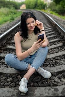 Gelukkige vrouw zittend op de spoorweg in zomerdoek, spoorlijnen, lifestyle