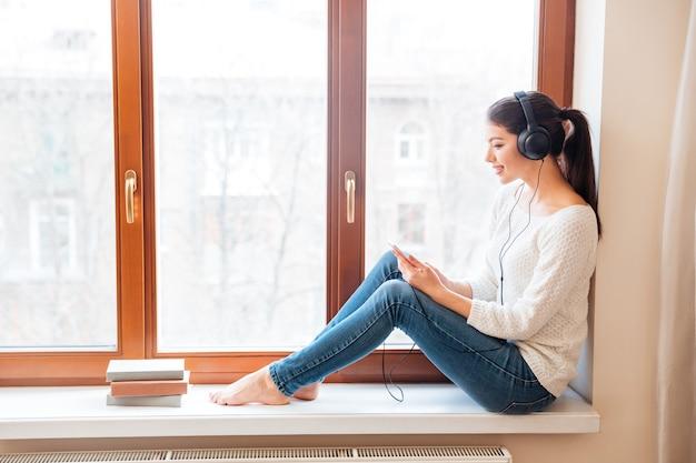 Gelukkige vrouw zittend op de vensterbank en het gebruik van smartphone met koptelefoon thuis
