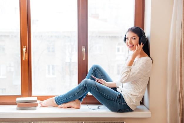Gelukkige vrouw zittend op de vensterbank met koptelefoon en kijkend naar de voorkant