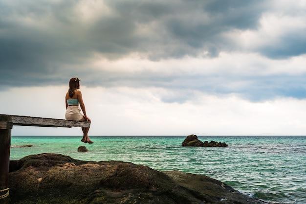 Gelukkige vrouw zittend op een houten brug in het zee strand van koh munnork island, rayong, thailand