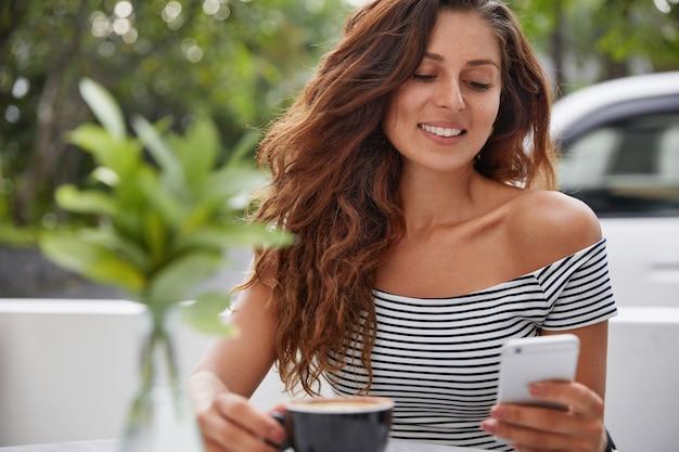 Gelukkige vrouw zittend op een koffieshop