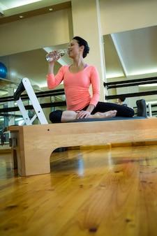 Gelukkige vrouw zittend op hervormer en drinkwater na training