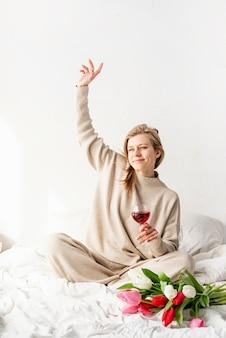 Gelukkige vrouw zittend op het bed in pyjama, met plezier genietend van bloemen en een glas rode wijn