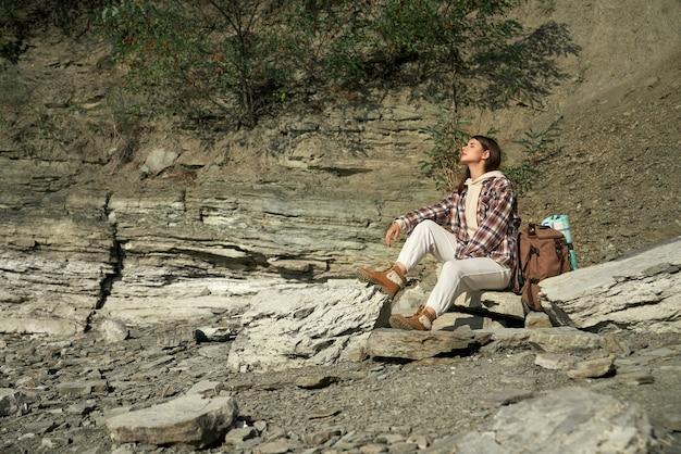 Gelukkige vrouw zittend op steen en genieten van zonnig weer