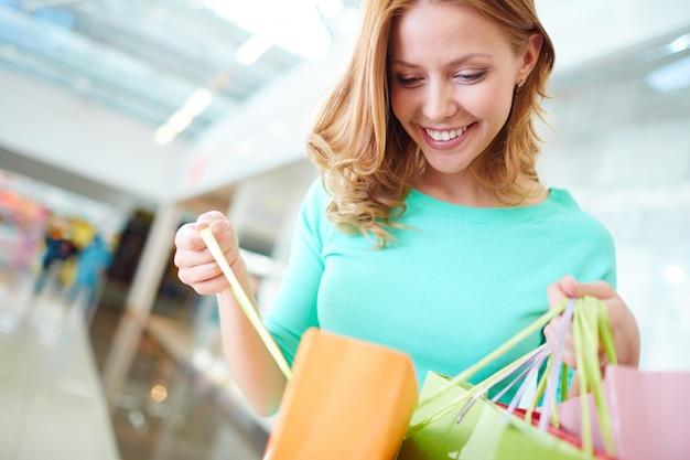 Gelukkige vrouw zoekt binnen boodschappentassen