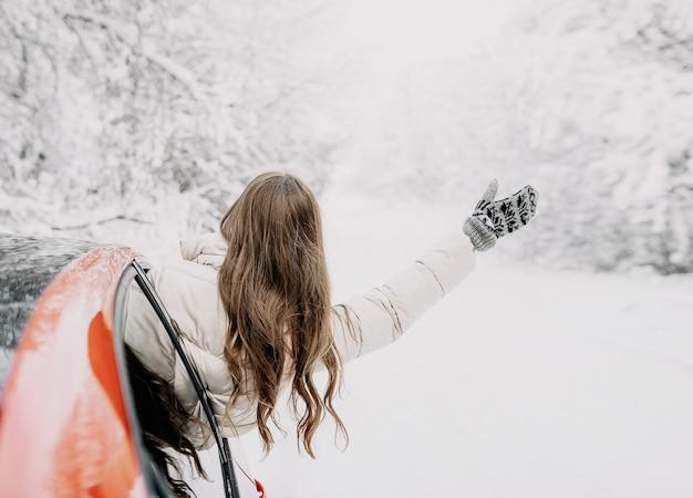 Gelukkige vrouw zwaaien vanuit stoel in auto tijdens het reizen