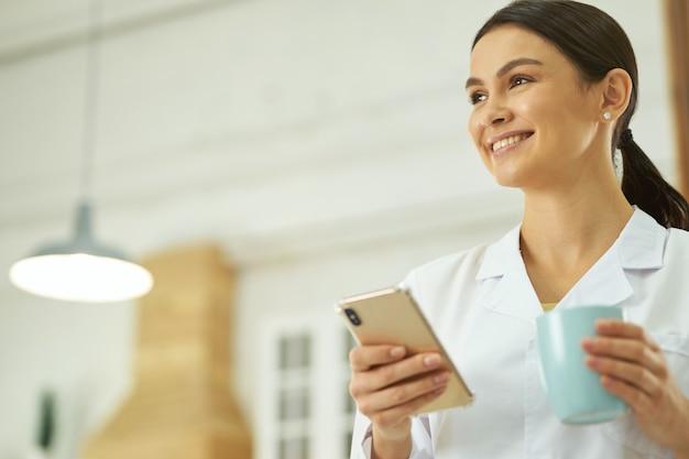 Gelukkige vrouwelijke arts die zich met smartphone en kop bevindt