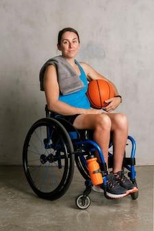 Gelukkige vrouwelijke atleet in een rolstoel met een basketbal