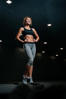 Gelukkige vrouwelijke atleet op de achtergrond van een zwarte zaal bereidt zich voor op een trainingssessie met touw