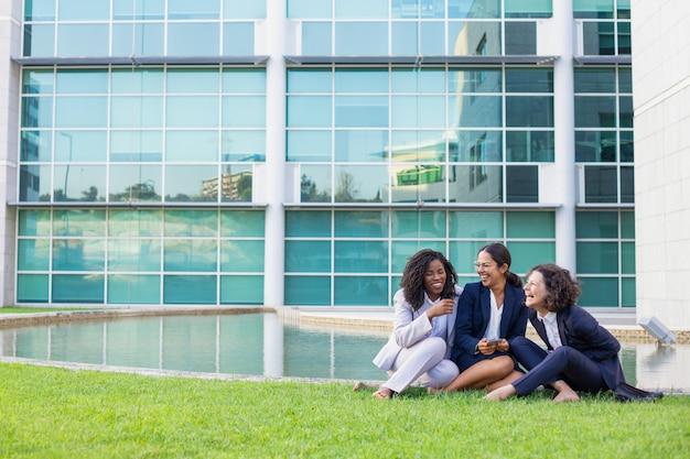 Gelukkige vrouwelijke bedrijfscollega's die van het werkonderbreking genieten
