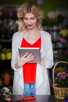 Gelukkige vrouwelijke bloemist die digitale tablet gebruiken