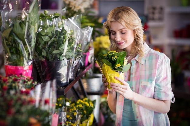 Gelukkige vrouwelijke bloemist die een bloemboeket ruikt