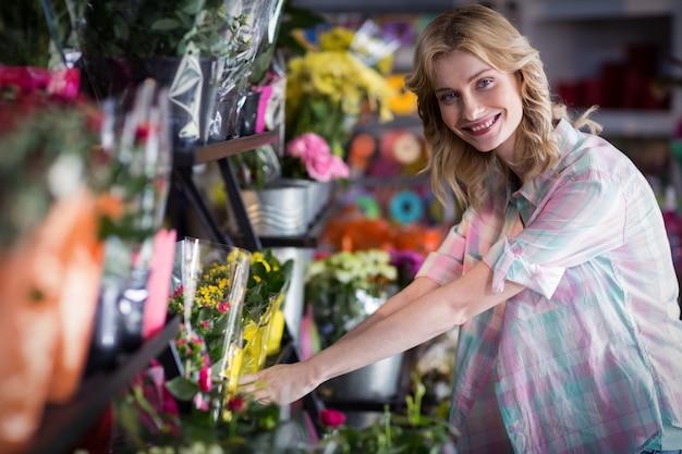 Gelukkige vrouwelijke bloemist die een bloemboeket voorbereidt