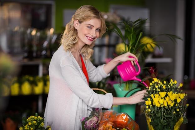 Gelukkige vrouwelijke bloemist het water geven bloemen