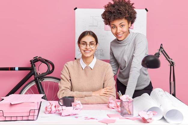 Gelukkige vrouwelijke collega's bereiden zich voor op een werksessie, hebben vrolijke uitdrukkingen die op het bureaublad poseren en in een goed humeur zijn poseren aan een bureau omringd door papieren blauwdrukkenschetsen. teamwerk concept