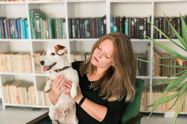 Gelukkige vrouwelijke eigenaar van jack russell terrier-hond, voelt zich verantwoordelijk voor het geven van huisdieren, staande tegen de achtergrond van boekenplanken. mensen en relatie met dieren