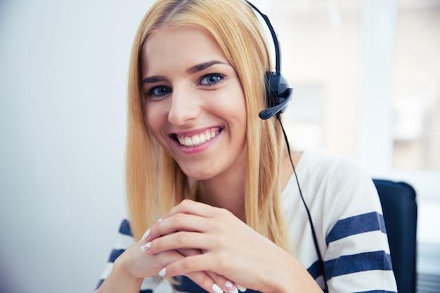 Gelukkige vrouwelijke exploitant in hoofdtelefoon