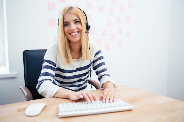 Gelukkige vrouwelijke exploitant met hoofdtelefoon