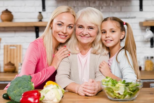 Gelukkige vrouwelijke generatie omringd door levensmiddel