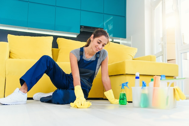 Gelukkige vrouwelijke huishoudster die vloer met detergentia en vod in appartement dweilen. schoonmaakdiensten concept.