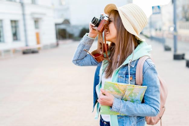 Gelukkige vrouwelijke kaart van de reizigersholding die in hand de foto op camera klikken